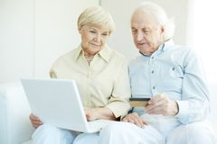 Online purchase. Senior couple with credit card and laptop during shopping through Internet Stock Photo