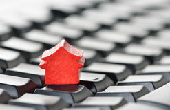 Online real estate concept. Miniature model home sitting on a computer keyboard. Web hosting or real estate on the Internet concept Royalty Free Stock Photo