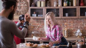 Online recipe blogging woman man dessert cooking. Online recipe. Blogging. Woman with dessert products. Man shooting vlog episode on cakes and pastries cooking royalty free stock images