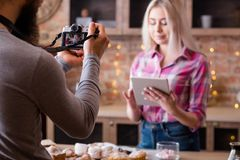 Online recipe blogging woman man vlog cooking. Online recipe. Blogging. Woman with tablet. Man shooting vlog episode on cakes and pastries cooking stock photography