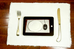 Online Restaurant Concept. Placemat with knife, fork, plate and computer tablet representing internet or online restaurant review, ordering or reservations Royalty Free Stock Photography