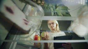 Online rozkazu jedzenie Młoda kobieta robi sklepowi spożywczemu spisywać dla sklepu spożywczego Patrzeje jedzenie w fridge, używa zdjęcie wideo