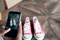 Online-säljarebruksmobiltelefonen tar ett foto av produkten för uploa royaltyfri fotografi
