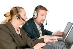 Online sales support team. Online sales or support team, one man and one women, consulting about a problem or a solution on their laptop PC. Isolated over white stock photo