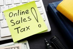 Online sales tax on a keyboard and money. Online sales tax on the keyboard and money royalty free stock photos