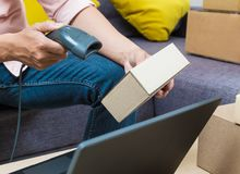 Online seller man using barcode scanner scanning one of his prod. Uct boxes, good for online selling business concept Stock Image