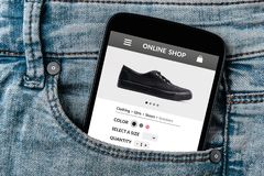 Online shop concept on smartphone screen in jeans pocket. All screen content is designed by me. Flat lay Royalty Free Stock Images