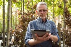 Online-Shop-Manager mit einem Klemmbrett in den Händen auf einem Hintergrund eines Gewächshauses lizenzfreies stockbild