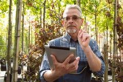 Online-Shop-Manager mit einem Klemmbrett in den Händen auf einem Hintergrund eines Gewächshauses stockbilder
