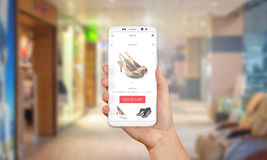 Online shop on mobile phone display. Modern white smart phone with round edges in girl hand. Shopping mall in background Stock Photo