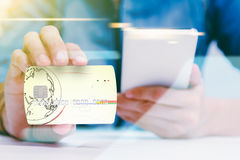 The online shoping card and holding credit card with hand for pa Royalty Free Stock Images