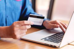 Online-shoppa begrepp för kreditkortdatasäkerhet, händer som rymmer kreditkorten och använder den smarta telefonen eller bärbara  fotografering för bildbyråer