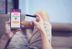 Online-shoppa begrepp - ung man som direktanslutet använder smartphoneshopping i websitemarknad, och händer som rymmer kreditkort royaltyfri bild