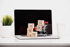 Online-shoppa ecommerce- och hemsändningbegrepp: Pappers- lådor med shoppa en vagns- eller spårvagnlogo på en bärbar dator arkivfoton