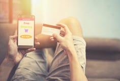 Online-shoppa man som direktanslutet använder smartphoneshopping i websitemarknad, och händer som rymmer kreditkorten fotografering för bildbyråer