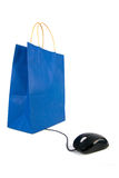 Online shopping. A computer mouse going to a shopping bag on white background Royalty Free Stock Photos