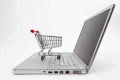 Online shopping. Miniature shopping cart on laptop on white background Royalty Free Stock Photo