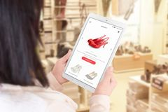Online shopping app on tablet display. Woman use tablet to search ecommerce web site. Shoe store in background royalty free stock photos