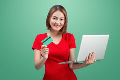 Online shopping. Asian woman holding laptop and credit card read. Y to pay stock photo