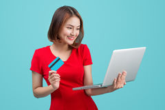 Online shopping. Asian woman holding laptop and credit card read Royalty Free Stock Photography