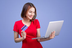 Online shopping. Asian woman holding laptop and credit card read Royalty Free Stock Photos