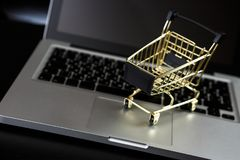 Online shopping bank card nearby a laptop and mini shopping cart. Online shopping. A laptop and mini shopping cart and gadgets royalty free stock image