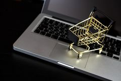 Online shopping bank card nearby a laptop and mini shopping cart. Online shopping. A laptop and mini shopping cart and gadgets royalty free stock photos