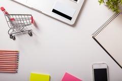 Online shopping. Shopping cart, keyboard, bank card. Online shopping. Bank card nearby a laptop and mini shopping cart on white background top view Royalty Free Stock Image