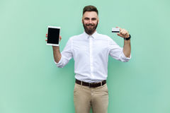 Online shopping or banking. Young adult businessman holding hands credit card and tablet and looking at camera and toothy smile. Stock Photos