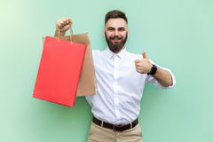 Online shopping or banking. Young adult businessman thumbs up and looking at camera and toothy smile. Royalty Free Stock Photos