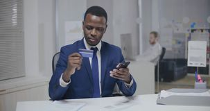 Online shopping. Black young man in attire using credit card. And mobile phone to pay for purchases stock video