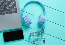 Online shopping. Buyer concept,. Consumer. Laptop, headphones, smartphone, toy shopping trolley on blue wooden background. Top view stock image