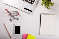 Online shopping. Shopping cart, keyboard, bank card. Online shopping. Bank card nearby a laptop and mini shopping cart on white background top view stock photography