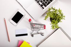 Online shopping. Shopping cart, keyboard, bank card. Online shopping. Bank card nearby a laptop and mini shopping cart on white background top view royalty free stock photography