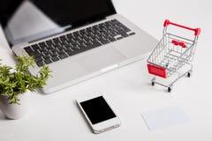 Online shopping. Shopping cart, keyboard, bank card. Online shopping. Bank card nearby a laptop and mini shopping cart on white background top view stock image