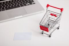 Online shopping. Shopping cart, keyboard, bank card. Online shopping. Bank card nearby a laptop and mini shopping cart on white background top view royalty free stock photos