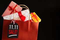 Online shopping of China, 11.11 single day sale concept. Shopping bag and gifts boxes with message tag stock photo