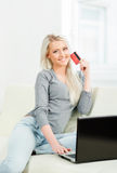 Online shopping concept. Beautiful blond girl with a credit card Stock Photography