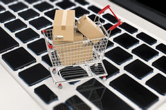 Online shopping concept with carton boxes in shopping cart stock illustration