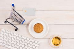 Online shopping concept. Computer keyboard, shopping cart, cake stock photo