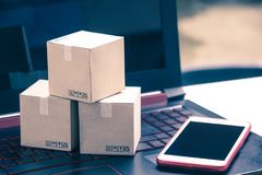 Online shopping concept e-commerce delivery buying service. squa. Re cartons shopping on laptop keyboard, showing customer order via the internet and smartphone royalty free stock photos