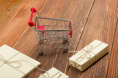 Online shopping concept - Empty Shopping Cart, laptop and tablet pc, gift box on rustic wooden background Royalty Free Stock Photo