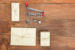 Online shopping concept - Empty Shopping Cart, laptop and tablet pc, gift box on rustic wooden background Royalty Free Stock Image