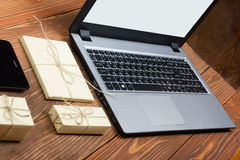 Online shopping concept - Empty Shopping Cart, laptop and tablet pc, gift box on rustic wooden background Stock Image