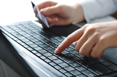 Online shopping concept. Female hands using laptop keyboard and holding credit card for online shopping Stock Image