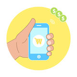 Online shopping concept with hand holding smartphone and e-commerce basket icons. Stock Photos