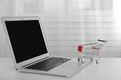 Online shopping concept. Laptop with mini market trolley Stock Images