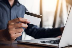 Online shopping concept with man hand using laptop and looking credit card for purchase order product stock image
