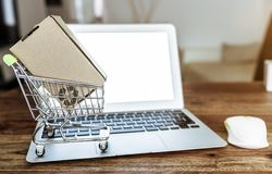 Online shopping concept with miniature shopping cart and laptop computer on table stock image