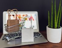 Online shopping concept with miniature shopping card and shopping bags on laptop computer royalty free stock photography